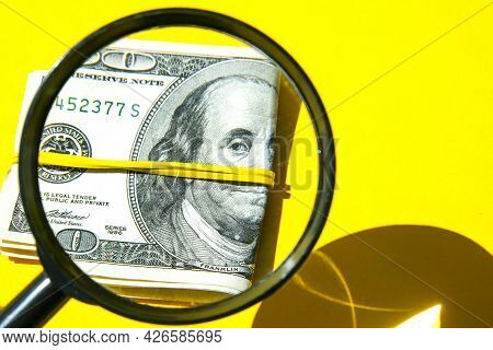 Magnifying Glass On The Background Of A Bundle Of Dollars Close-up, One Hundred Dollars Franklin, On