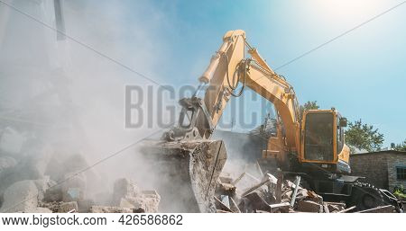 Destruction Of Old House By Excavator. Bucket Of Excavator Breaks Concrete Structure.