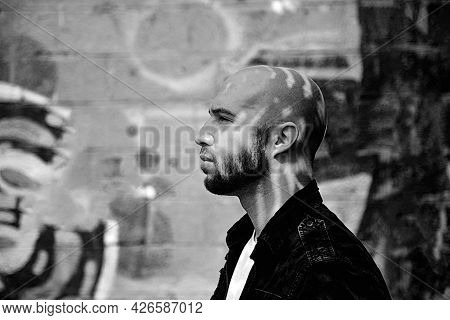 Young Dangerous Gang Member Looking At Something On The City Street. Concerned Bald Man Thinking Of