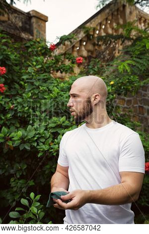 Serious, Concerned Man Working In A Park Full Of Blooming Trees. Young Caucasian Male Farmer In A Gr