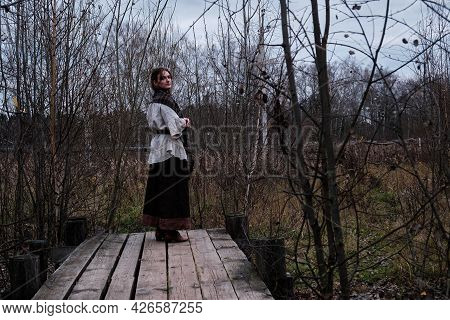 Full-length Woman On An Old Wooden Platform From Boards In Retro Style. Vintage Clothes On The Woman