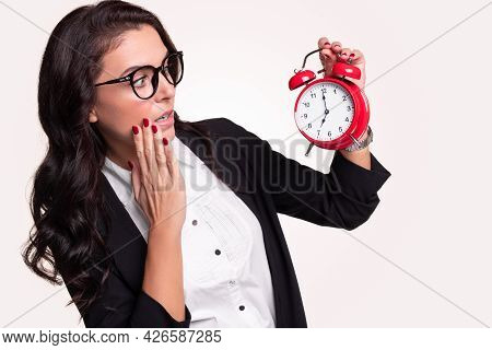 Stunned Adult Business Lady In Formal Outfit And Glasses Looking At Red Alarm Clock With 7 O Clock T