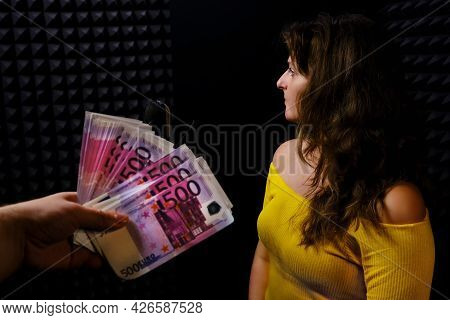 The Woman Turns Away From The Money On A Black Background. Refusal To Receive Euro In The Recording