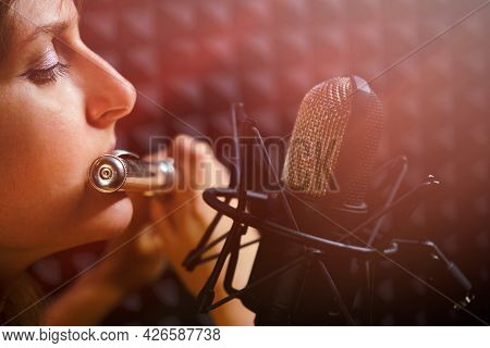 Woman Flutist Playing The Large Orchestral Flute, Close-up. Female Flute Player Plays In Recording S