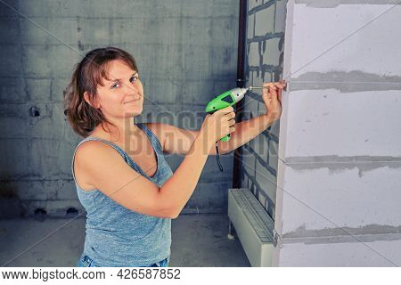 A Young Woman Screws A Screw Into The Wall, Copy Space. Repairs In The Apartment Alone. Woman With A