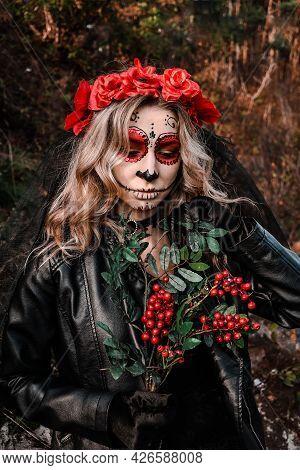 Closeup Portrait Of Calavera Catrina. Young Woman With Sugar Skull Makeup And Red Flowers. Dia De Lo