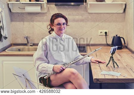 A Woman Is Sitting With A Flute In The Kitchen In Front Of The Phone. Quarantine Flute Training For