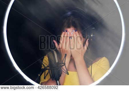 A Young Woman Covers Her Face With Her Hands Next To The Microphone. Vocalists And Singers Have Voic