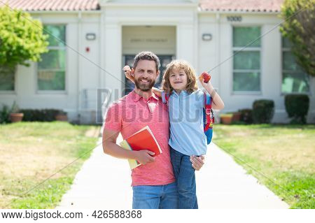 Father Walking Son To School. Parent And Pupil Of Primary School With Backpack.