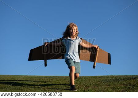 Child Boy Playing With Toy Airplane Wings. Kids Dream Of Becoming A Pilot. Superhero Flying.