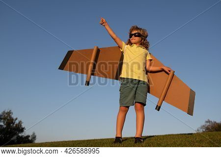 Kid Superhero With Jetpack. Boy Pilot Against A Blue Sky. Child Pilot Play On Summer Day. Success, L