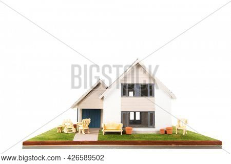 Miniature house with garden furniture isolated over white background
