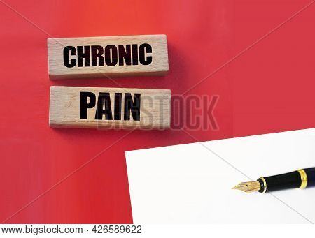 Chronic Pain Words On Wooden Blocks On Red Background. Medicine Healthcare Concept.