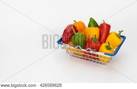 Miniature Grocery Cart Filled With Colorful Peppers. Supermarket Basket With Paprika.