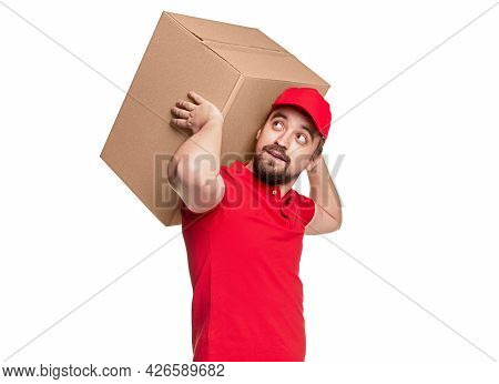 Adult Bearded Male Courier In Red Uniform Carrying Heavy Big Carton Package While Delivering Parcel