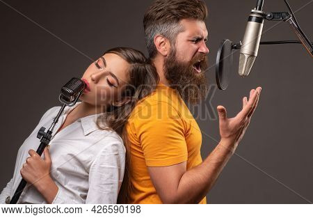 Couple Singing. Karaoke Singers. Man And Young Woman Singing With Music Microphone.