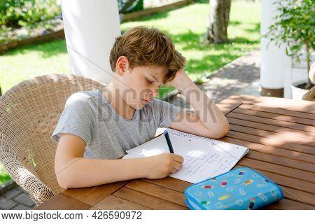 Hard-working Sad School Kid Boy Making Homework During Quarantine Time From Corona Pandemic Disease.