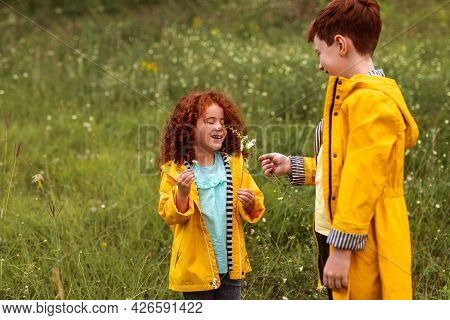 Cute Little Curly Haired Ginger Girl Smelling Flowers While Standing With Older Brother Dressed In S
