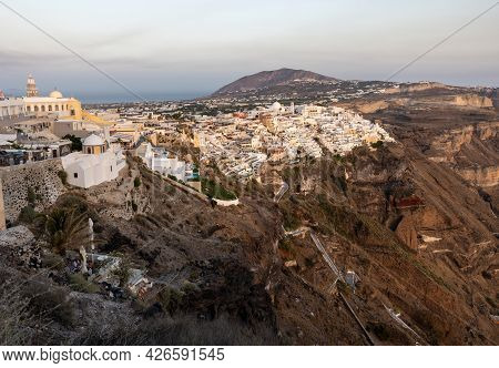 The Whitewashed Town Of Fira In Warm Rays Of Sunset On Santorini Island, Cyclades, Greece