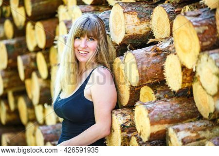 Beautiful Girl Stands Near Cut Logs In The Forest