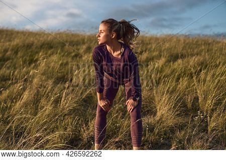 Active Fit Young Female Jogger In Sportswear Leaning On Knees And Looking Away While Relaxing After