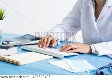 Close-up Of Female Doctor Hands Typing At Computer Keyboard. Physician In Medical Uniform Working At