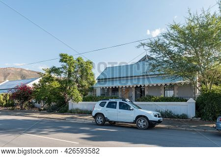 Prince Albert, South Africa - April 20, 2021: A Street Scene, With An Historic House And A Vehicle,