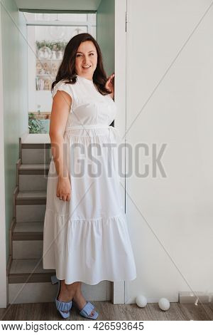 Attractive Woman In White Dress Stands In The Doorway By The Stairs.
