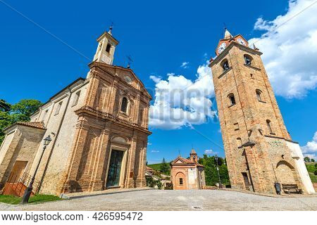 Old parish church, small chapel and bell tower under blue sky in town of Monforte d'Alba in Piedmont, Northern Italy.