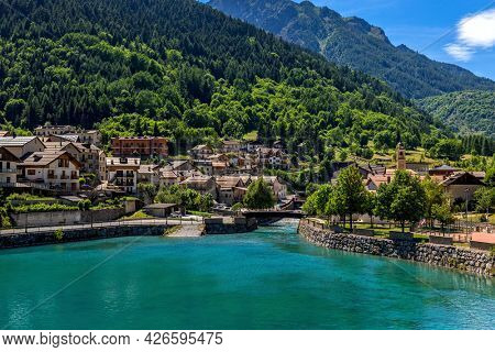 View from above of alpine lake surrounded by small town of Pietraporzio as mountains with green trees on background in Piedmont, Northern Italy.