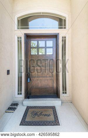 Exterior Of A Front Door With Glass Panels And Doormat