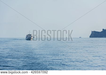 Yalta Crimea July 04, 2019. A Tourist Ship Is On The Horizon. People Come And Go From The Popular To