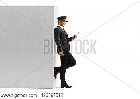 Full length profile shot of a chauffeur leaning on a wall and typing on a smartphone isolated on white background