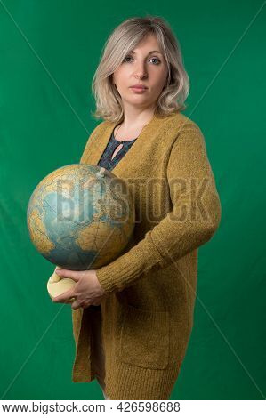 Adult Woman Posing With An Old Globe. Photos On School Subjects. Studio Photo With Chroma Key Backgr