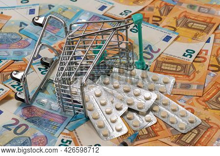 Shopping Cart With Tablets On Euro Bills Background, Concept Of Expensive Cost Of Healthcare