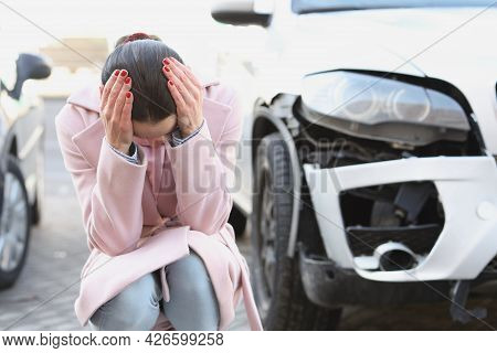 Upset Young Woman Sits With Head Bowed Next To Wrecked Car