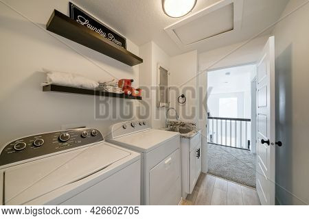 Laundry Room Interior With Laundry Machines And Vanity Sink