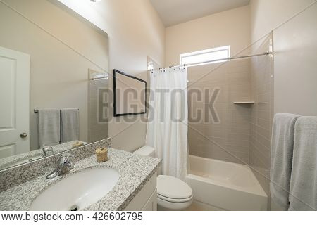 Bathroom Interior With Vanity And Tub With Light Brown Rectangular Wall Tiles And Window