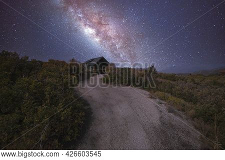 Path In The Middle Of A Shrubland Leading To A House Under An Aesthetic Composite Milky Way