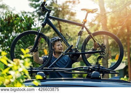 Man Takes Mountain Bike From The Car Roof Rack
