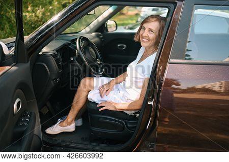 Happy Senior Woman Driving Sitting In New Brown Car, Smiling Looking At Camera Enjoying Journey.driv