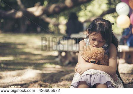 Sad Girl Hugging Teddy Bear Sadness Alone In Green Garden Park. Lonely Girl Feeling Sad Unhappy Sitt
