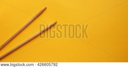 View From Above On Wooden Chopsticks On A Yellow Background. Sticks Are On The Left Side. Food Appli