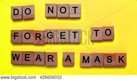 The Word, Do Not Forget To Wear A Mask, Is Made Of Wooden Blocks On A Yellow Background. Antiviral M