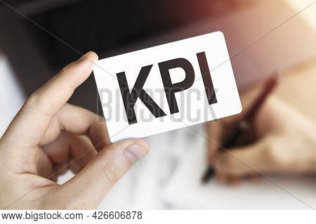 Close Up Of Hand Business Person Keeps Card With Text Kpi - Key Performance Indicators. Document, Pe
