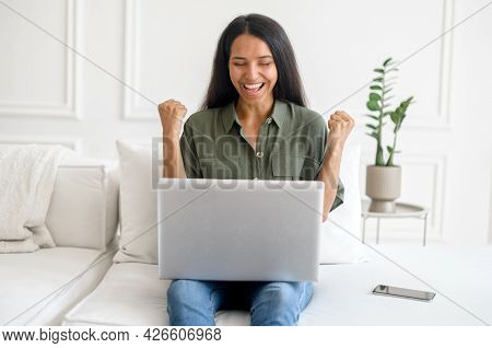 Lucky One. Excited Indian Young Woman Celebrating Online Win, Great Deal Or Business Success, Sittin