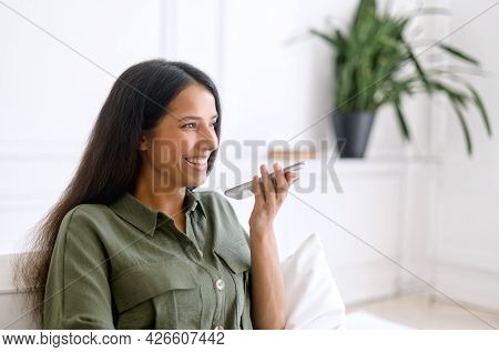 Charming Indian Woman Is Recording Voice Message And Smiling, Sits On The Sofa At Home And Holding S