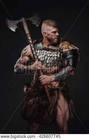 Brutal Tattooed Warrior Wearing Light Armour And Fur Holding Two-handed Axe In Dark Studio