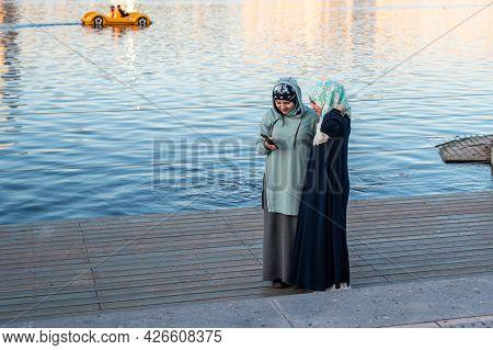Kazan, Russia - May 08 2021: Muslim Ladies In Hijabs And Long Dresses Look At Phone Standing On Grou