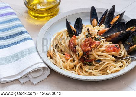 Linguini Pasta With Mussels In A Plate Close-up On A Table With A Jug Of Olive Oil, High Key, Close-